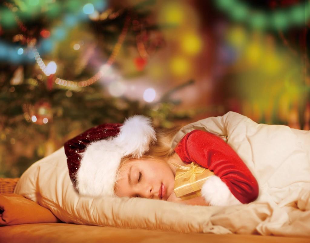 Little cute blond boy sleeping under Christmas tree